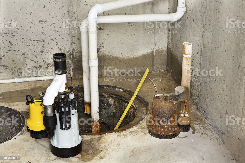 Replacing the old sump pump in a basement stock photo
