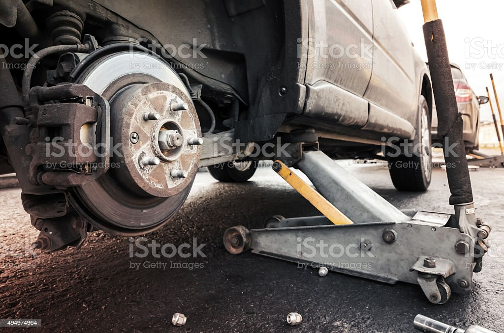 Replacing wheels on a car, jack holds the body stock photo