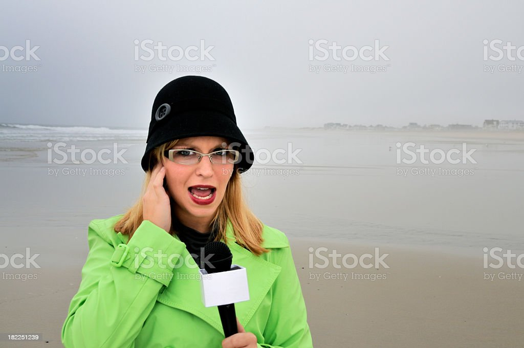 Reporter on Stormy Beach with Concerned Look royalty-free stock photo