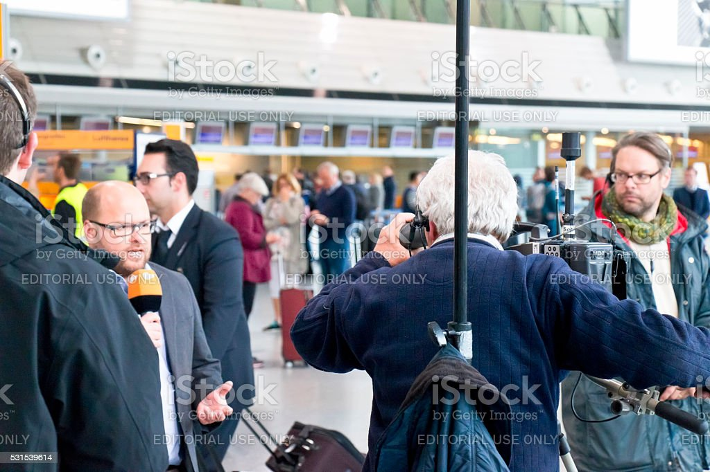 TV reporter reporting from a strike at the Frankfurt Airport stock photo