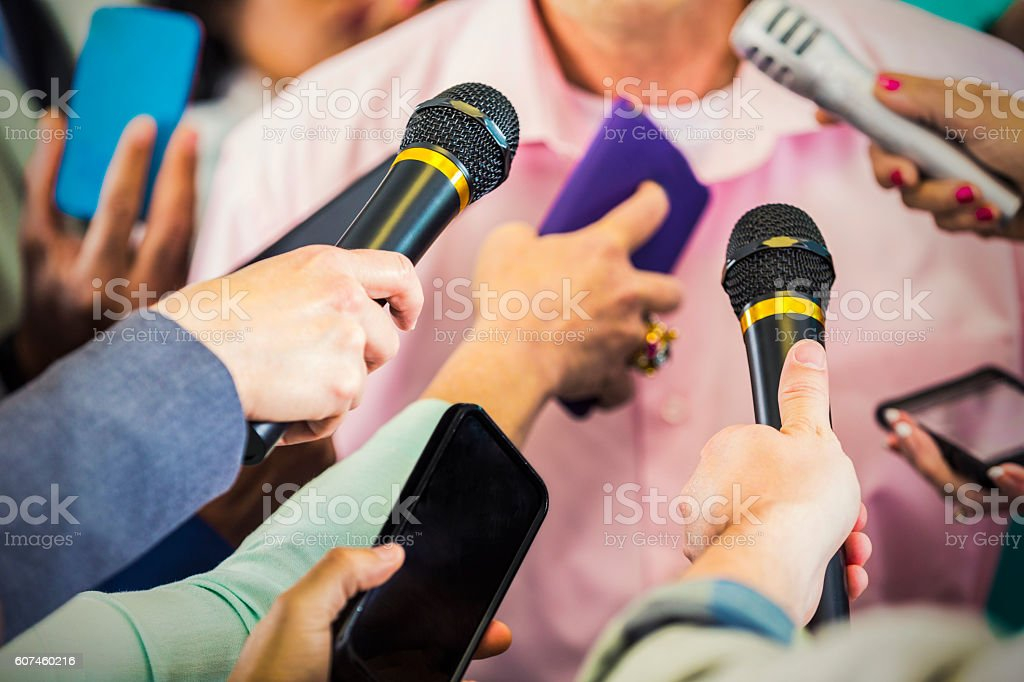 Reporters ask male political candidate questions stock photo