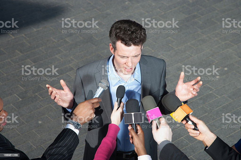 Reporters holding microphones for politician royalty-free stock photo