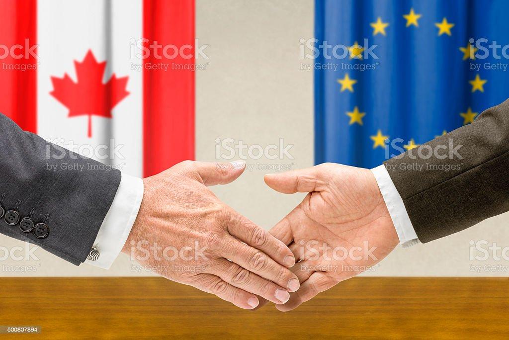 Representatives of Canada and the EU shake hands stock photo