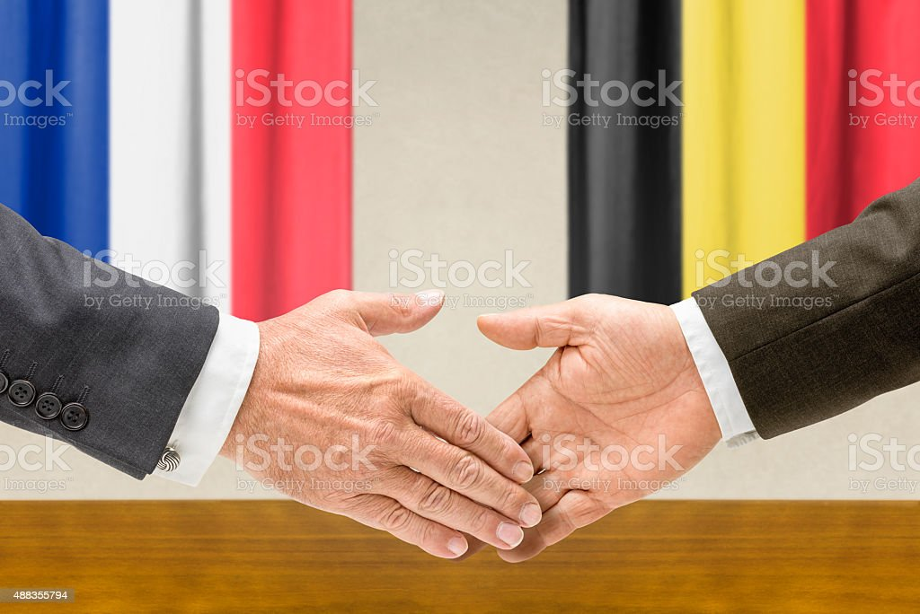 Representatives of France and Belgium shake hands stock photo