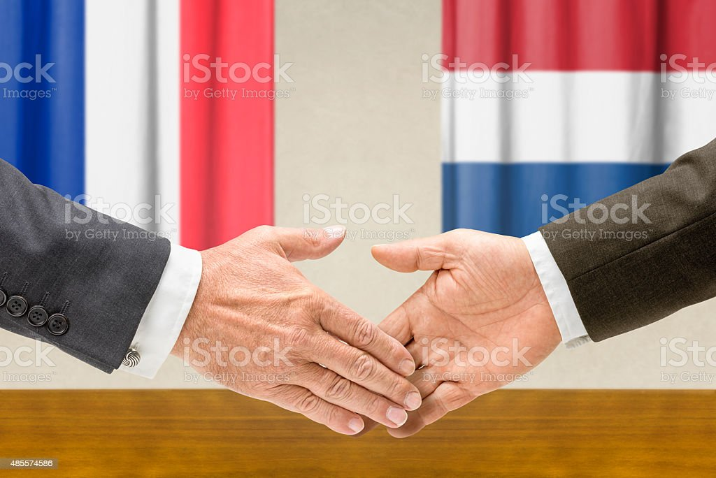Representatives of France and the Netherlands shake hands stock photo