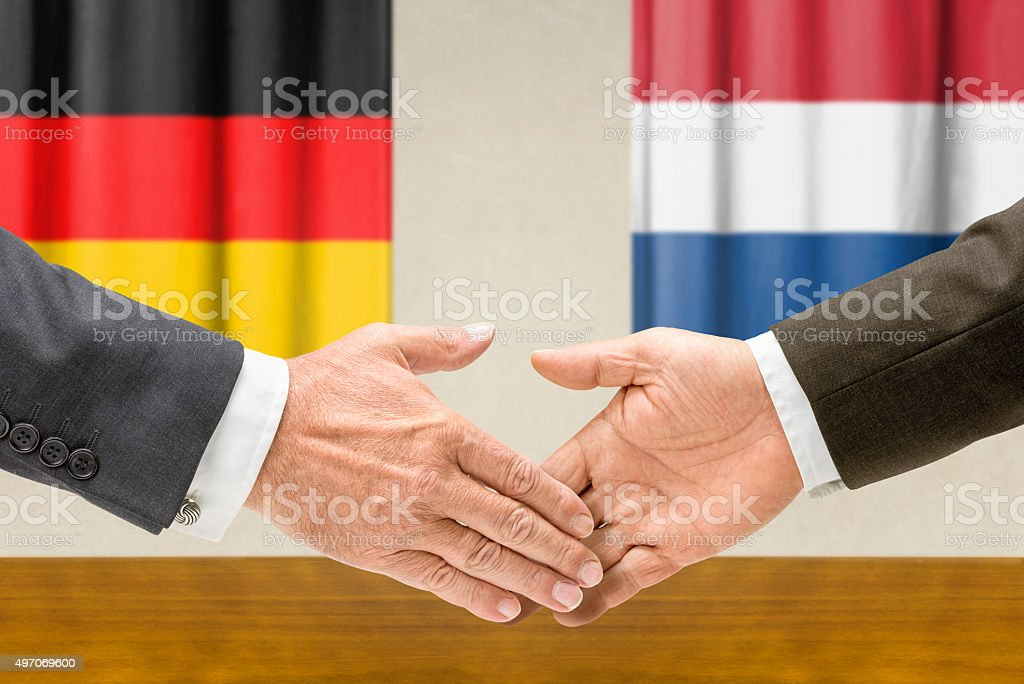 Representatives of Germany and the Netherlands shake hands stock photo