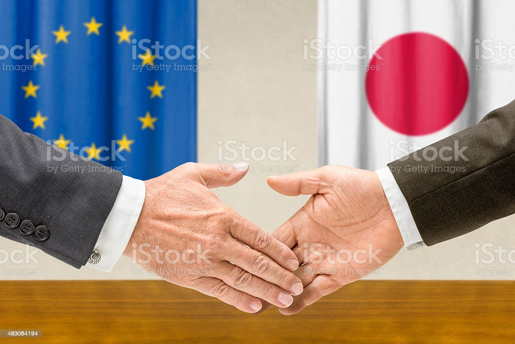 Representatives of the EU and Japan shake hands stock photo