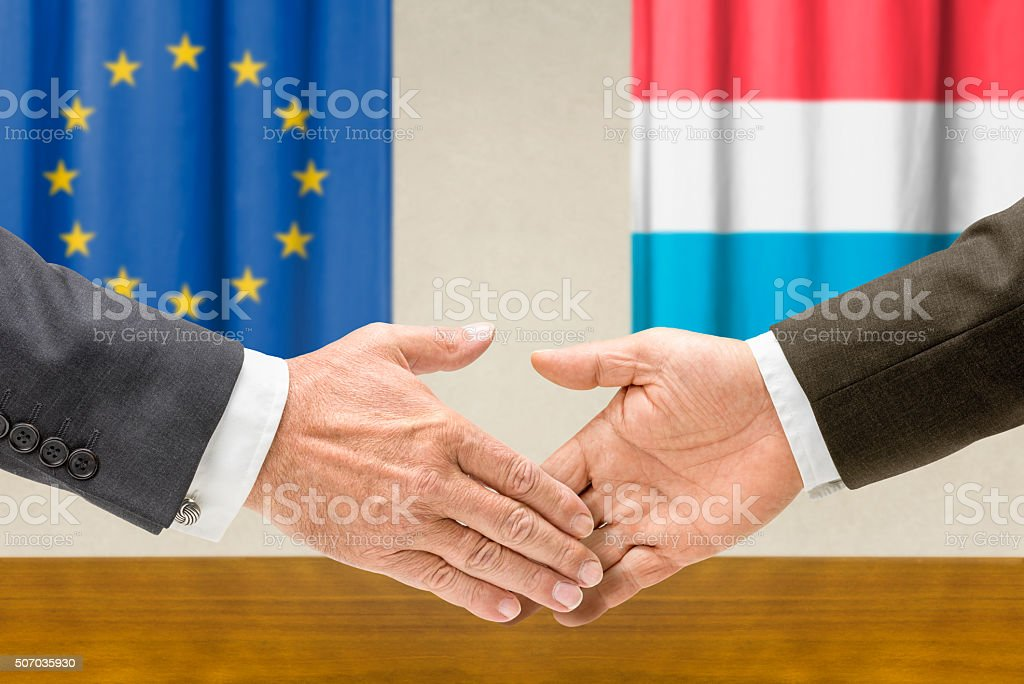 Representatives of the EU and Luxembourg shake hands stock photo