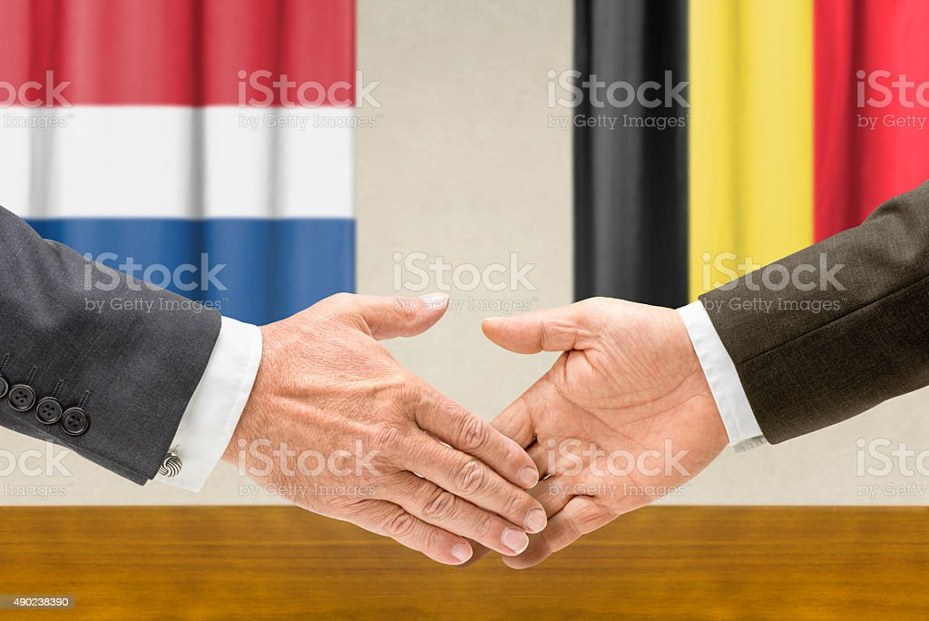 Representatives of the Netherlands and Belgium shake hands stock photo