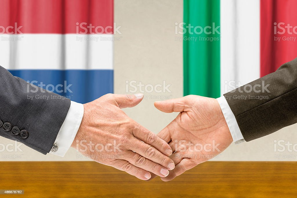Representatives of the Netherlands and Italy shake hands stock photo