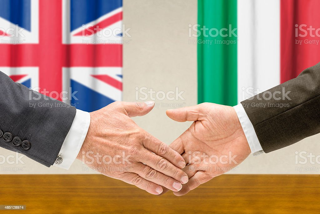 Representatives of the UK and Italy shake hands stock photo