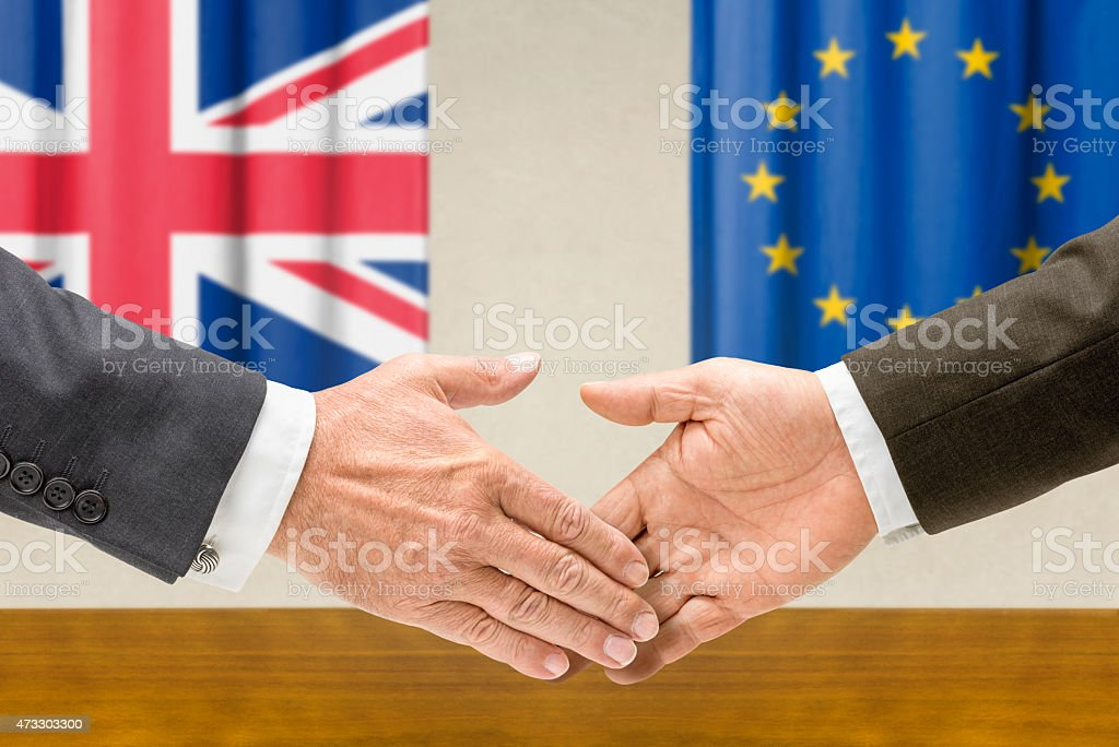 Representatives of the UK and the EU shake hands stock photo