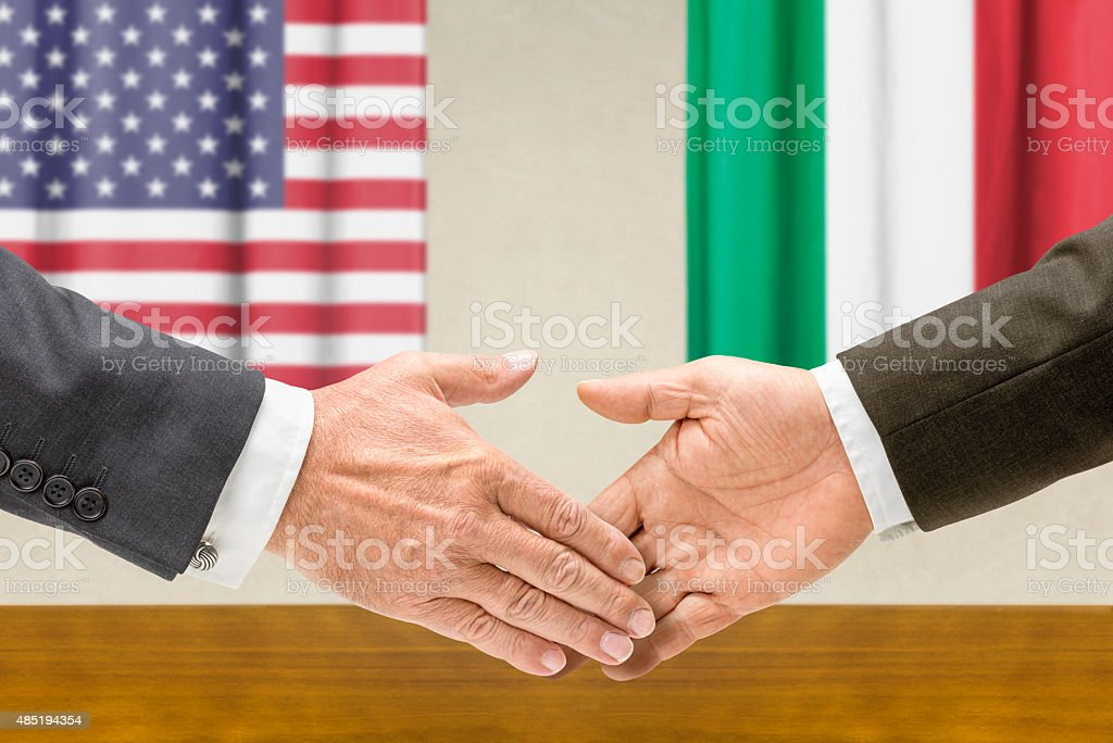 Representatives of the USA and Italy shake hands stock photo