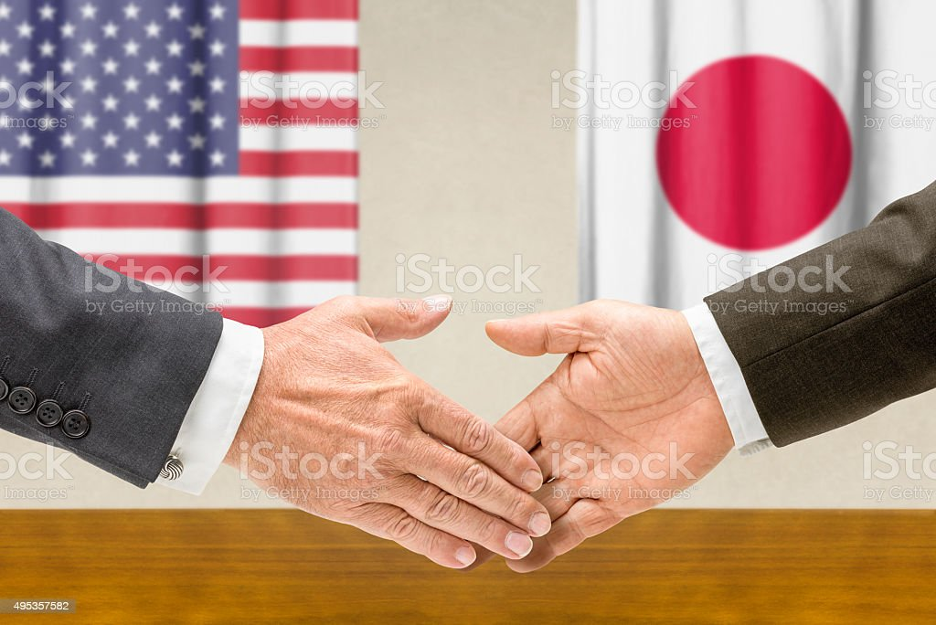 Representatives of the USA and Japan shake hands stock photo