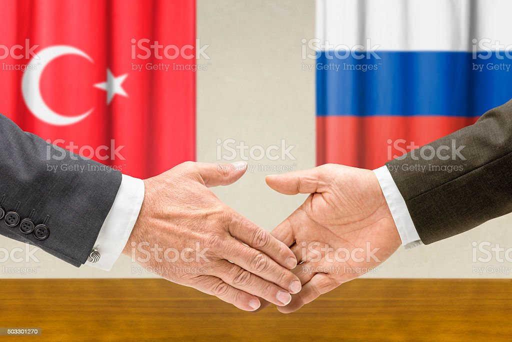 Representatives of Turkey and Russia shake hands stock photo
