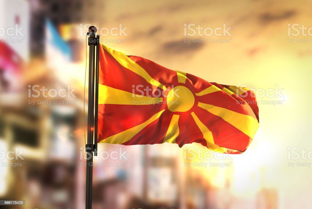 Republic of Macedonia Flag Against City Blurred Background At Sunrise Backlight stock photo