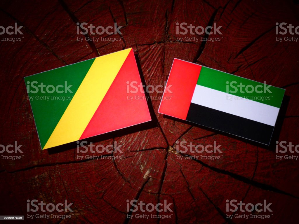 Republic of the Congo flag with United Arab Emirates flag on a tree stump isolated stock photo