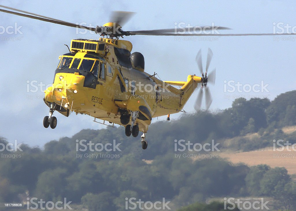 Rescue helicopter hovers over hills stock photo