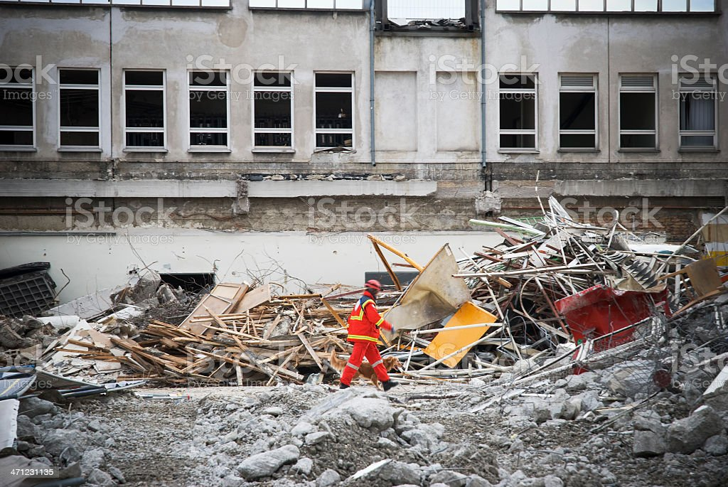 Rescue man walking on demolished building debris stock photo