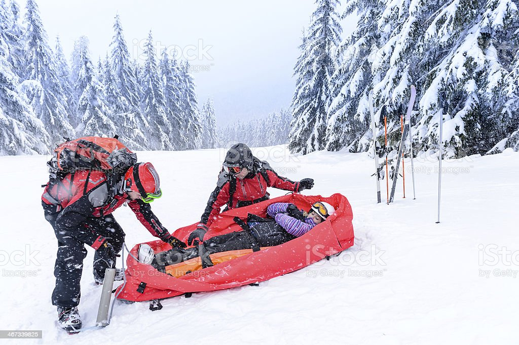 Rescue of injured woman by ski patrol sled on snowy mountain stock photo