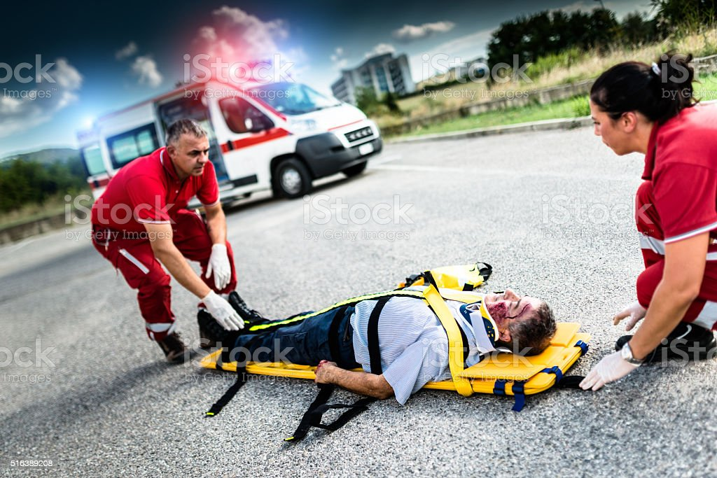rescue team helping injured man stock photo