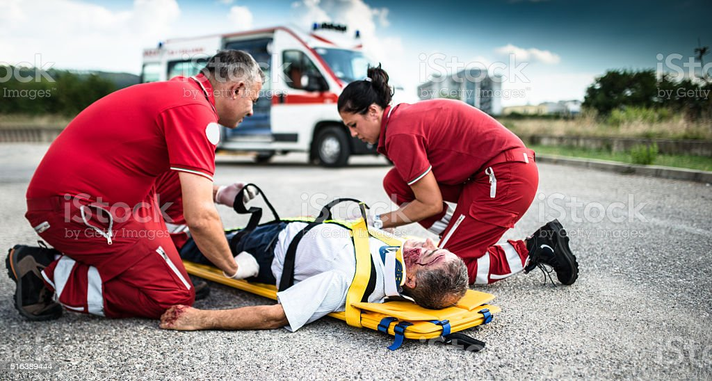 rescue team helping injured man stock photo
