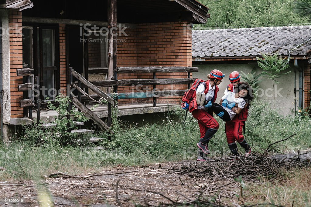 Rescue team saving a victim after natural disaster stock photo