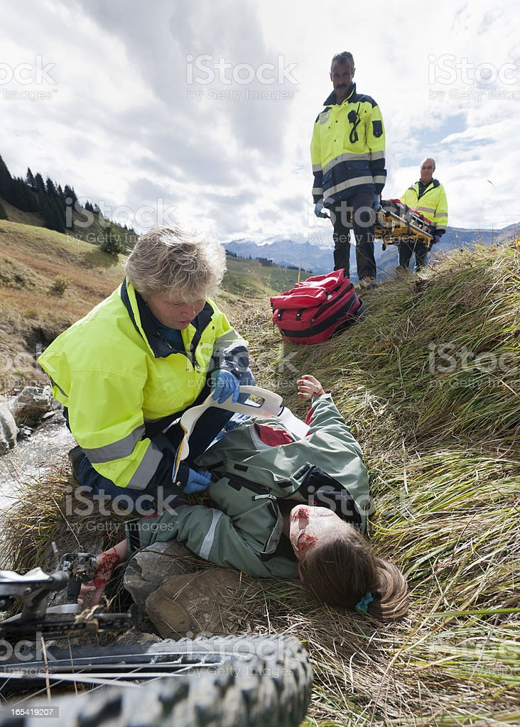 rescue worker attending to mountain bike accident victim royalty-free stock photo