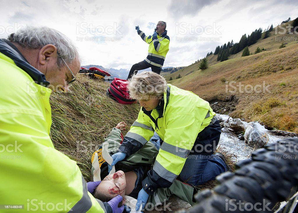 rescue workers attending to mountain bike accident victim with a neck...