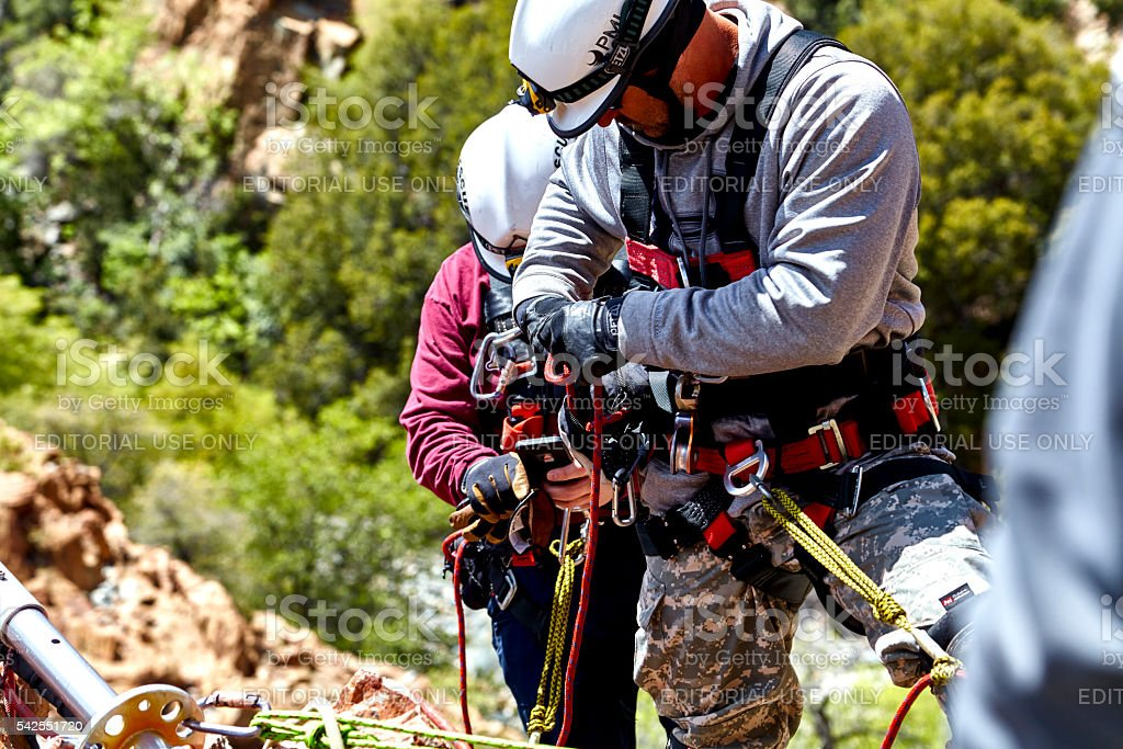 Rescue Workers practicing a Rescue Drill on Ledge of Mountain stock photo