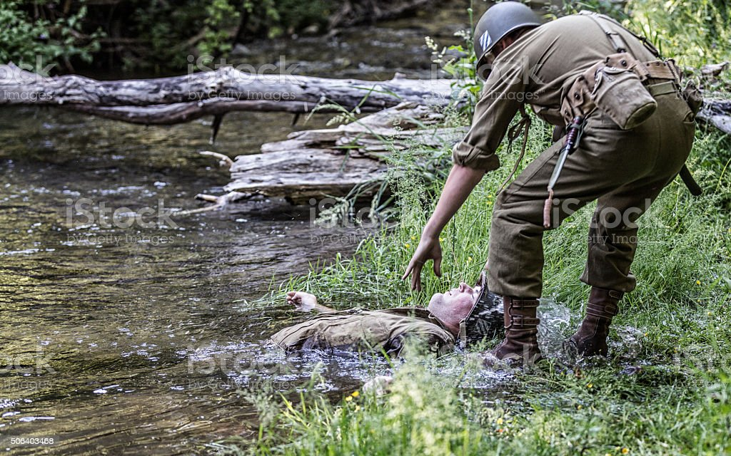 Rescuer Reaching For Wounded WWII US Army Combat Casualty Soldier stock photo