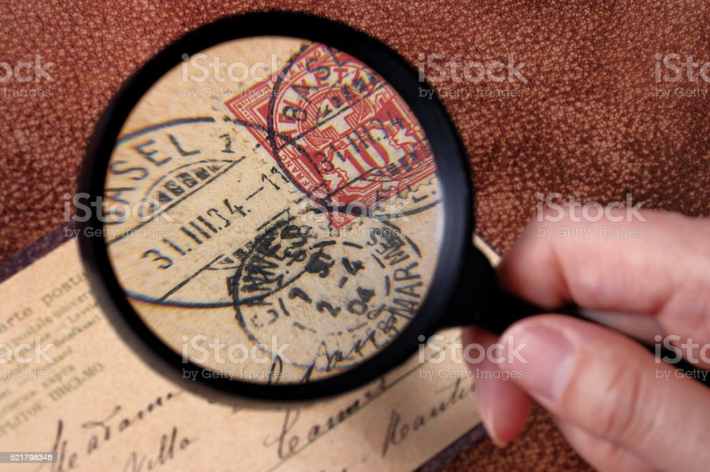research on philately with magnifier stock photo