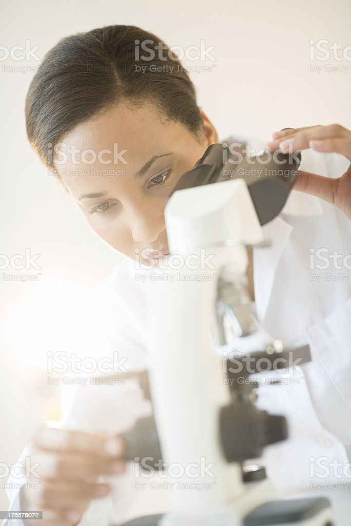 Researcher Adjusting Microscope In Laboratory royalty-free stock photo
