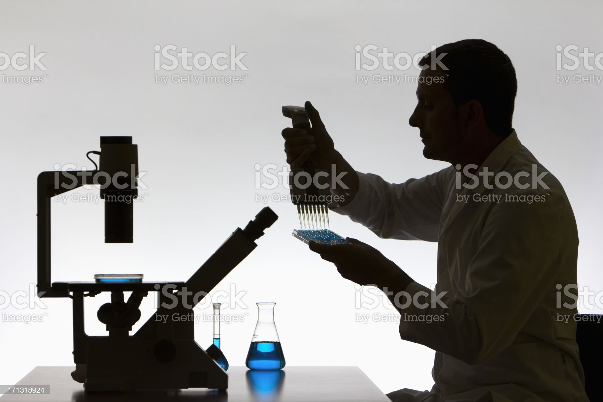 Researcher holding and injecting chemicals into a microtiter plate royalty-free stock photo