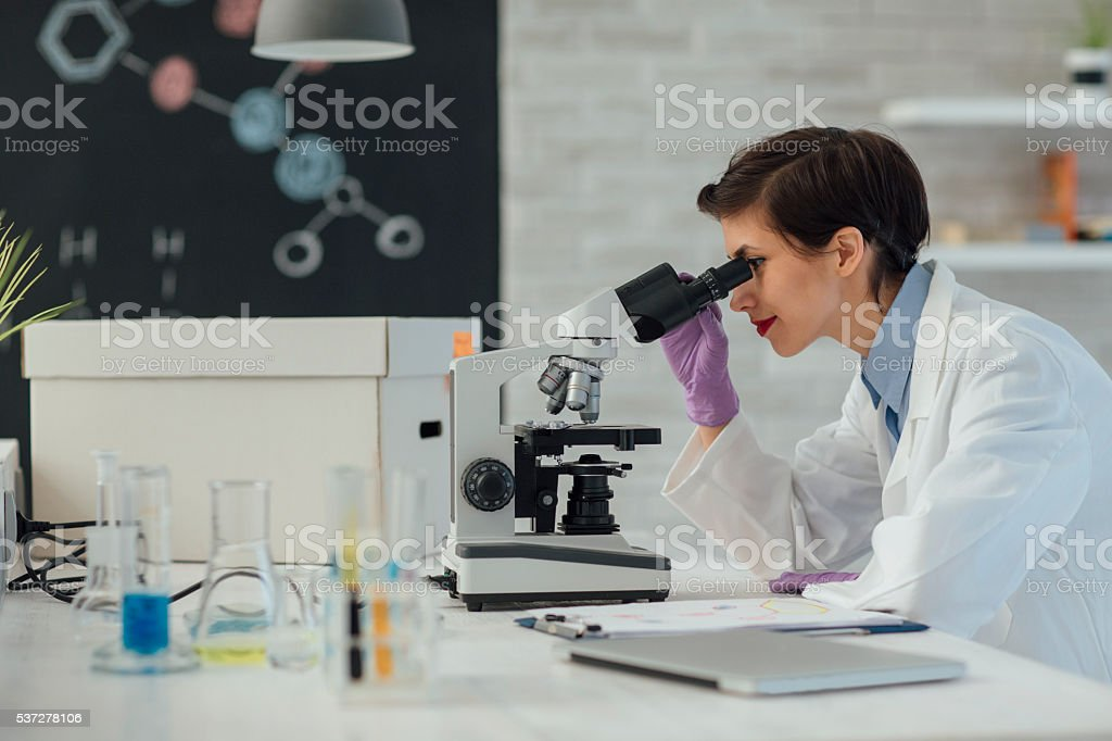 Researcher Using Microscope In Her Lab. stock photo