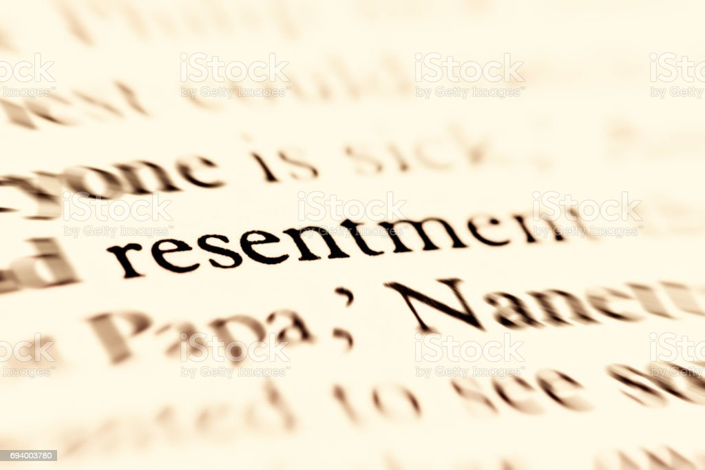 'resentment' in focus on page of defocused words stock photo