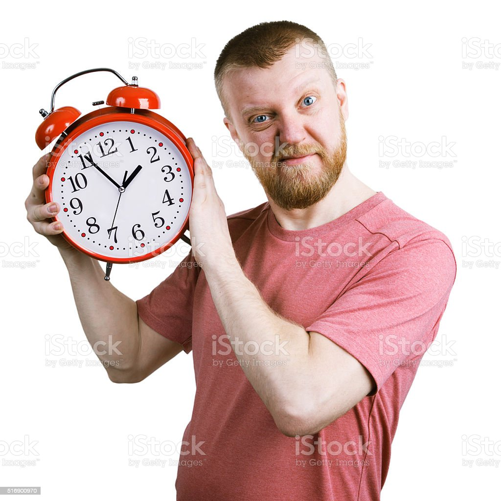 Resents bearded man with an alarm clock stock photo