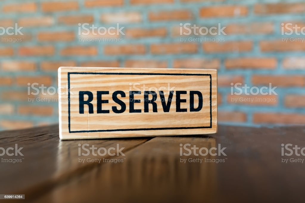 reserved sign on a wooden table in a restaurant stock photo