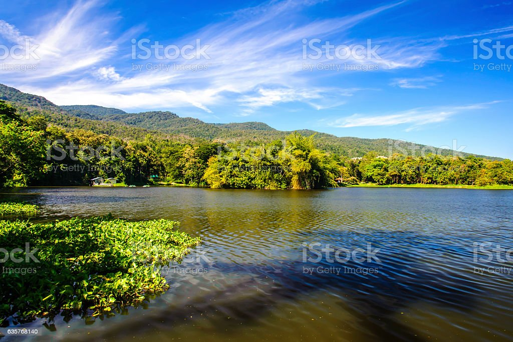 Reservoir under blue sky with a mountain backdrop stock photo