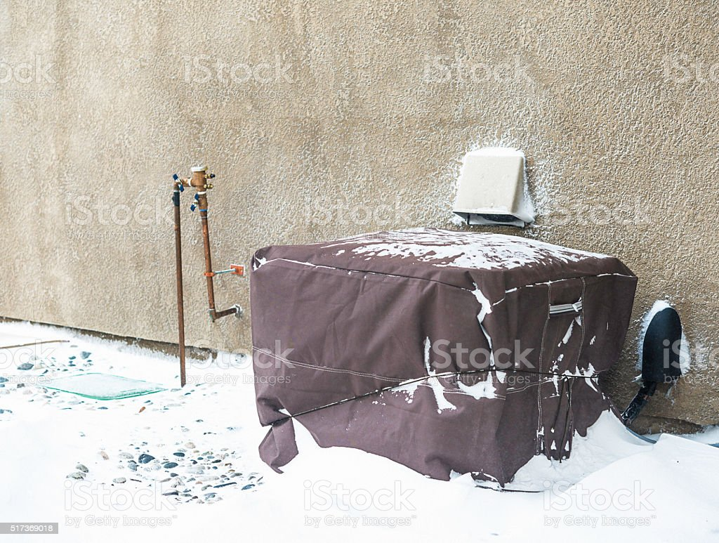 Residential air conditioning unit wrapped with protective cover in blizzard stock photo