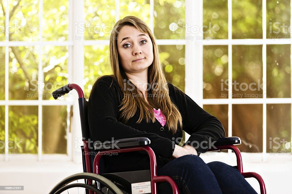 """Resigned young woman in wheelchair shrugs as if saying """"Whatever"""" stock photo"""