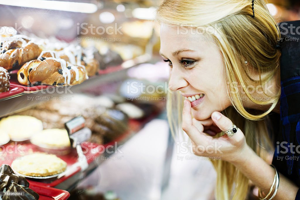 Resistance is futile! Blonde shopper checks cake display in bakery stock photo