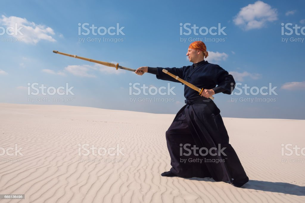 Resolute man with a training sword is practicing martial arts stock photo