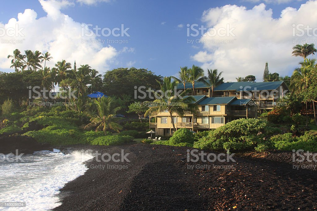 Resort hotel on black sand beach at Hana Maui stock photo