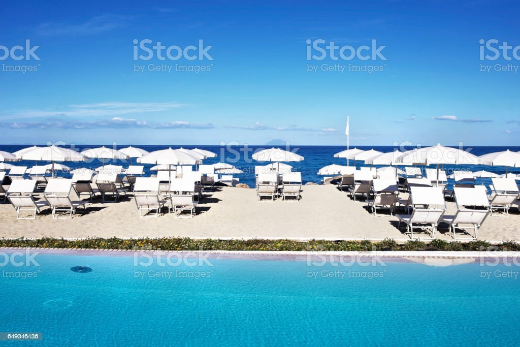 Resort:Resort swimming pool with lounge chairs and  beach parasols  near the sea stock photo