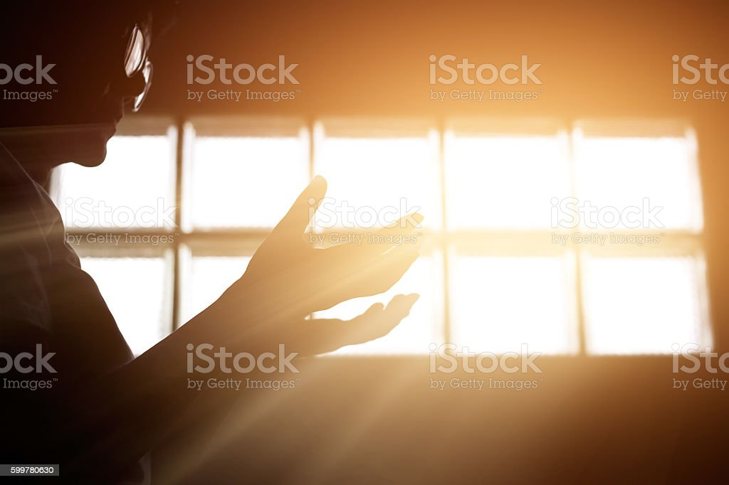 Respect and pray in the room with sunrise through window stock photo