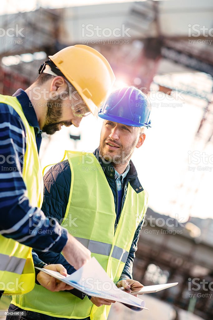 Responsible manager having discussion on construction site stock photo