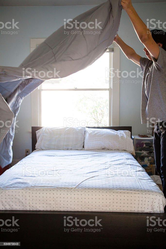 Responsible Young Man Making Bed stock photo