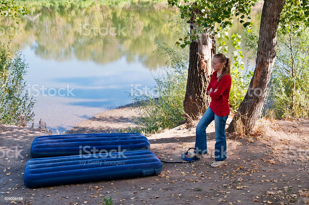 Rest at nature. Girl pumps up an inflatable mattress stock photo