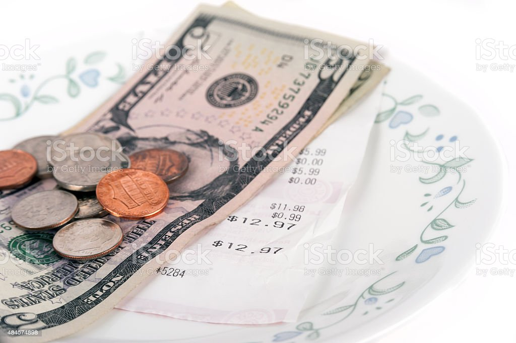 Restaurant bill with dollar bills on a plate and receipt stock photo